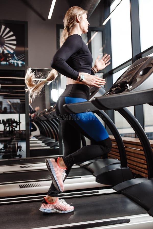 La muchacha atlética con el pelo rubio largo vestido en una ropa de deportes se está rodando en la rueda de ardilla delante de la fotografía de archivo libre de regalías