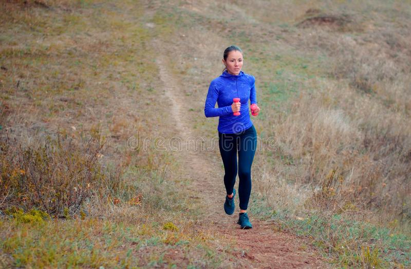 La muchacha atlética hermosa con pesas de gimnasia rosadas corre a lo largo de la colina imagenes de archivo