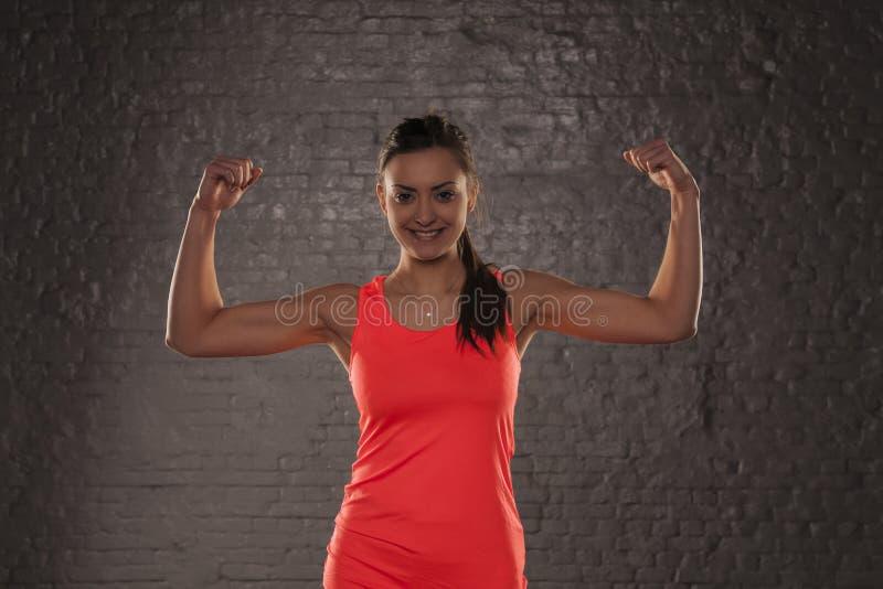 La muchacha atlética hermosa joven muestra sus músculos foto de archivo
