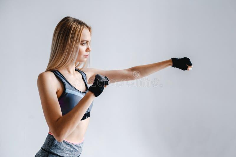 La muchacha atlética rubia en guantes toma un sacador imagen de archivo