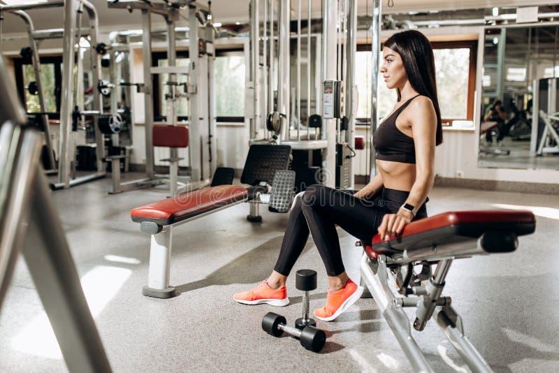 La muchacha atlética vestida en ropa negra del deporte se sienta en el banco en el gimnasio imagen de archivo libre de regalías