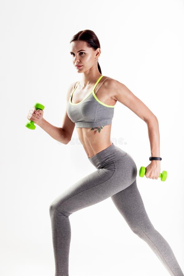 La muchacha atlética vestida en una ropa de deportes gris está haciendo ejercicios con pesas de gimnasia en el fondo blanco imagen de archivo libre de regalías