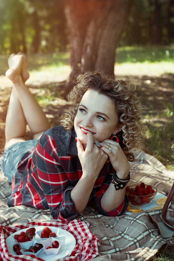 La muchacha atractiva con el pelo con curvas y las gafas de sol están en la comida campestre de la baya del verano foto de archivo
