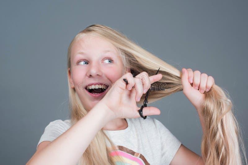 La muchacha atractiva del chaild está cortando su pelo natural rubio largo fotografía de archivo libre de regalías