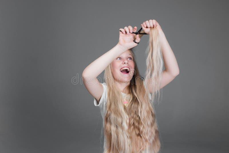 La muchacha atractiva del chaild está cortando su pelo natural rubio largo fotografía de archivo