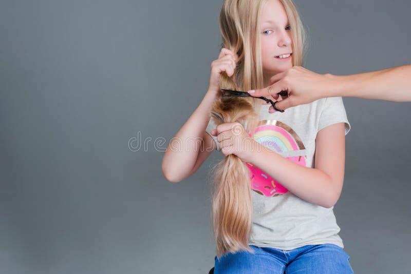 La muchacha atractiva del chaild está cortando su pelo natural rubio largo fotos de archivo libres de regalías