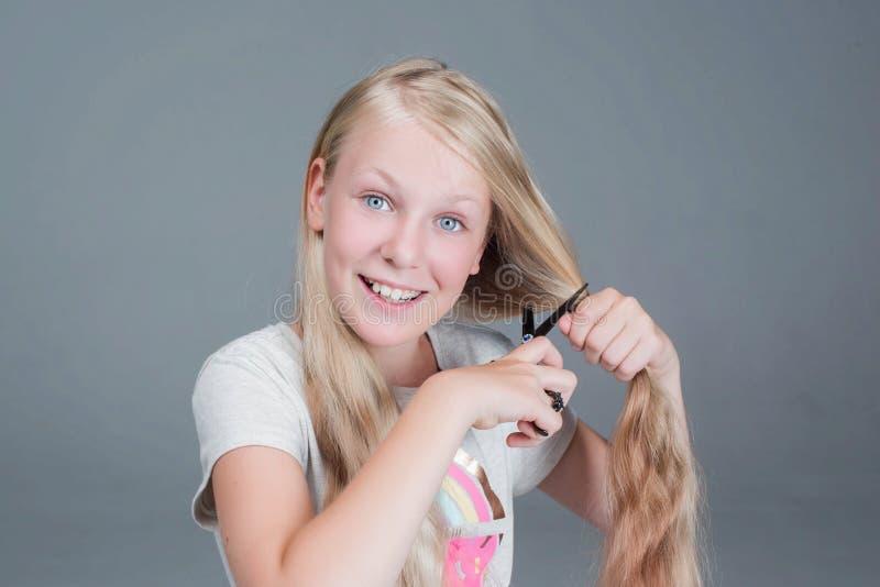 La muchacha atractiva del chaild está cortando su pelo natural rubio largo foto de archivo