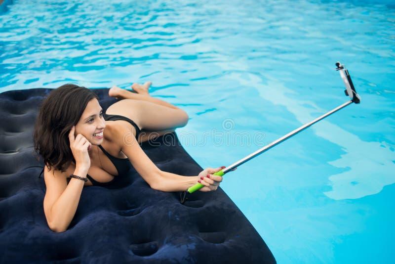 La muchacha atractiva en bikini que sonríe y hace la foto del selfie en el teléfono con el palillo del selfie en un colchón en la fotografía de archivo