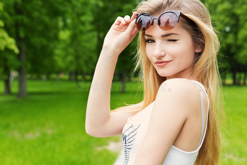 La muchacha atractiva feliz linda hermosa con el pelo largo rubio en la camiseta blanca levantó las gafas de sol y guiñó imagenes de archivo