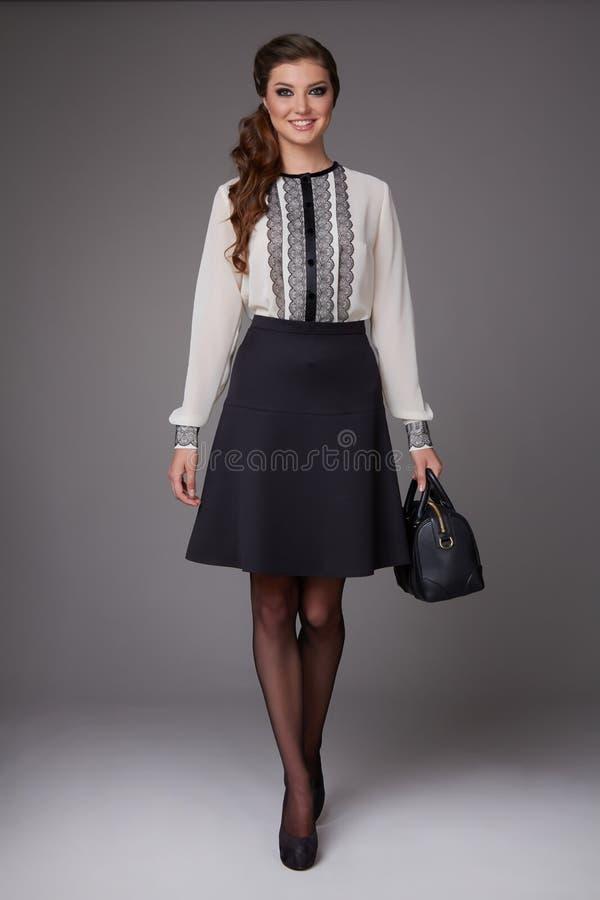 La muchacha atractiva hermosa en negocio viste en una falda corta a la blusa del rosa de la rodilla con los tacones altos imagen de archivo