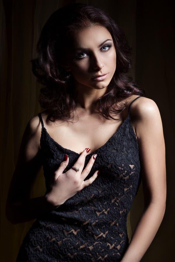 La muchacha atractiva hermosa joven con un maquillaje apacible y el pelo hermoso en un cordón negro se visten con la iluminación  imagenes de archivo