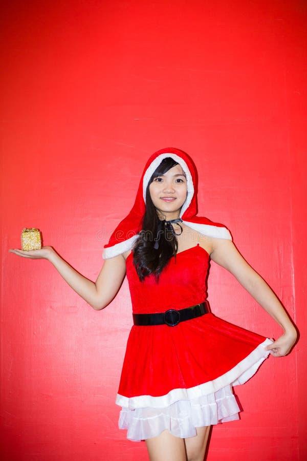 La muchacha atractiva hermosa que lleva a Papá Noel viste con la caja de regalo imagenes de archivo
