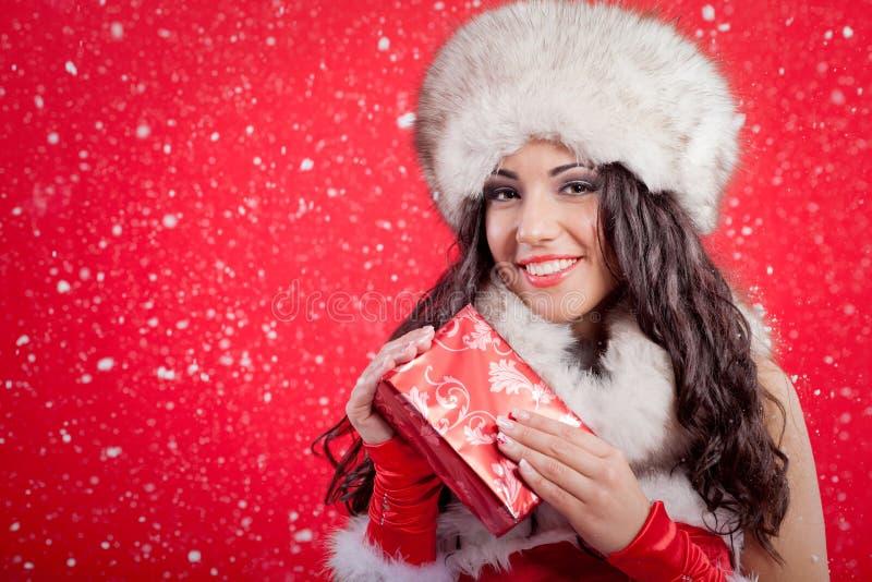 La muchacha atractiva hermosa que lleva a Papá Noel viste con la Navidad g foto de archivo libre de regalías