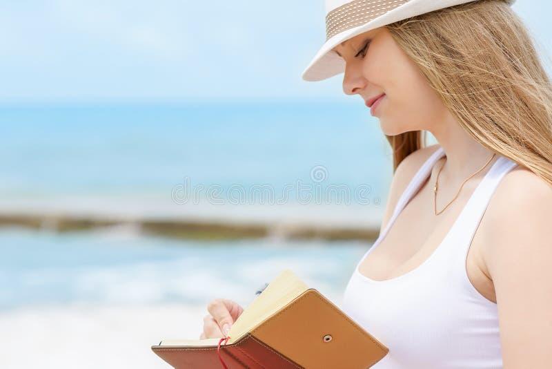 La muchacha atractiva joven con sonrisa buena está escribiendo cierta idea o letra en su cuaderno por la pluma en fondo del mar a foto de archivo