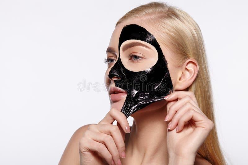 La muchacha atractiva joven saca la cara facial negra fotos de archivo libres de regalías
