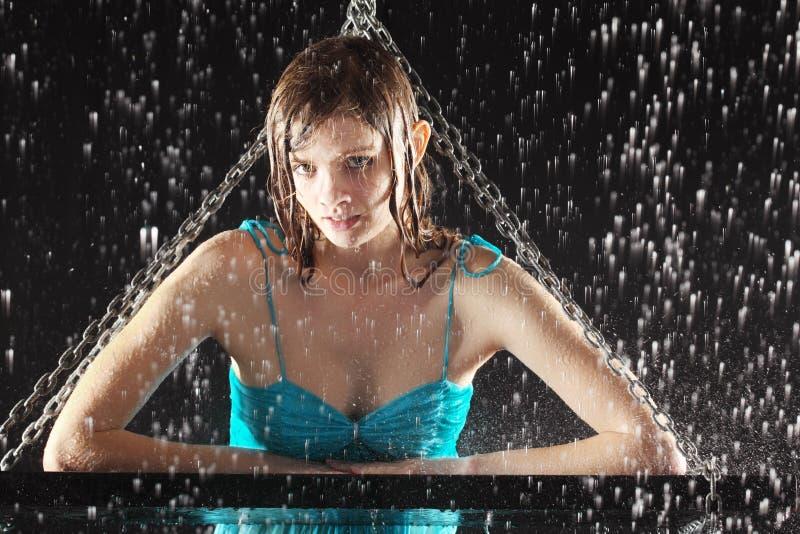 La muchacha atractiva mojada se inclinó en el oscilación con los encadenamientos