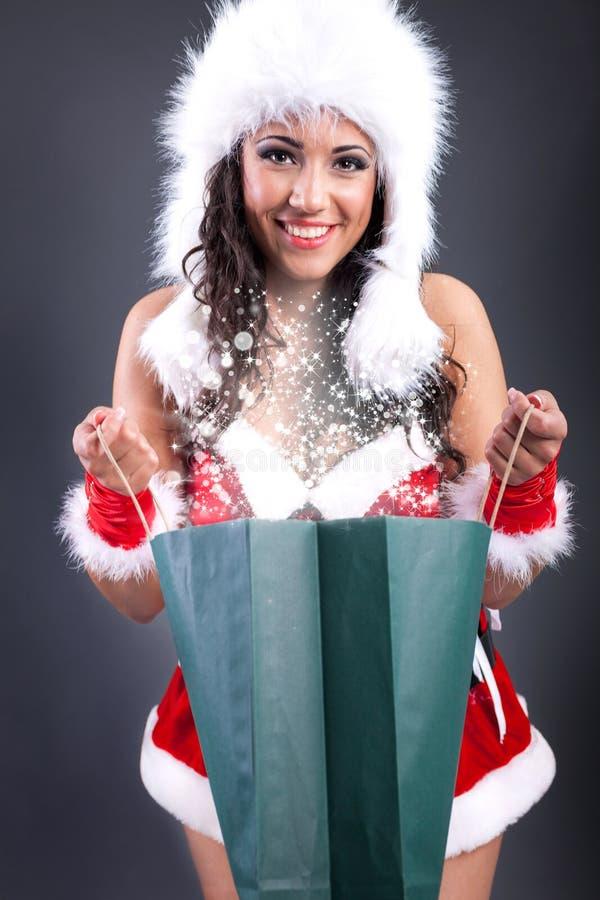 La muchacha atractiva que lleva a Papá Noel viste con el bolso mágico del color imágenes de archivo libres de regalías