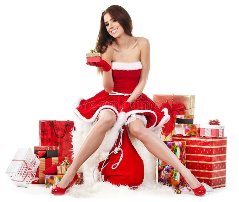 la muchacha atractiva que lleva a Papá Noel viste con la Navidad g fotografía de archivo