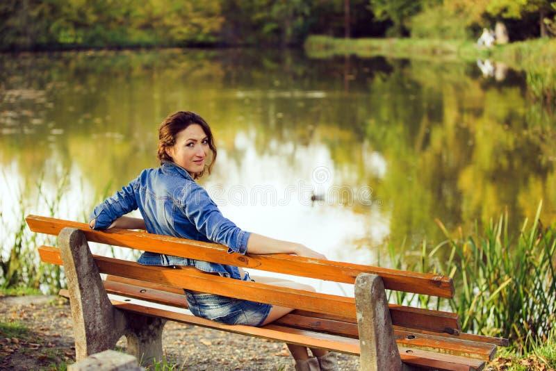 La muchacha atractiva que se sienta en un banco foto de archivo