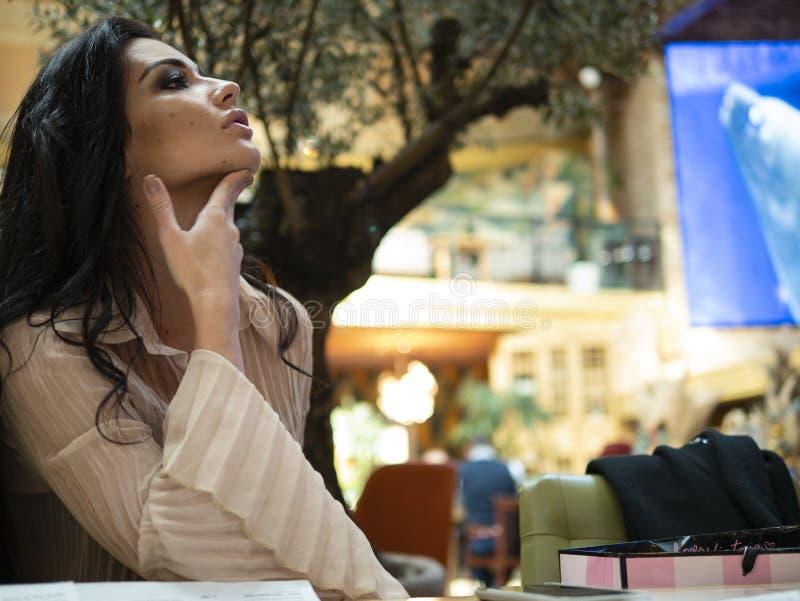La muchacha atractiva se sienta en barbilla del perfil y de los tactos imagenes de archivo