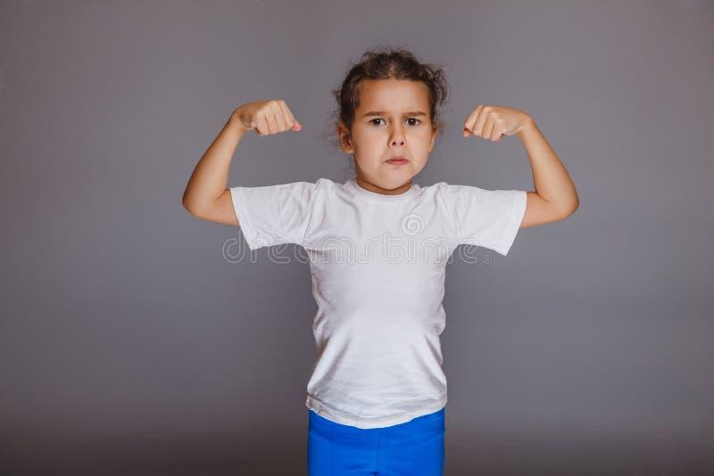 La muchacha aumentó sus manos para arriba que mostraban fuerza en gris foto de archivo libre de regalías
