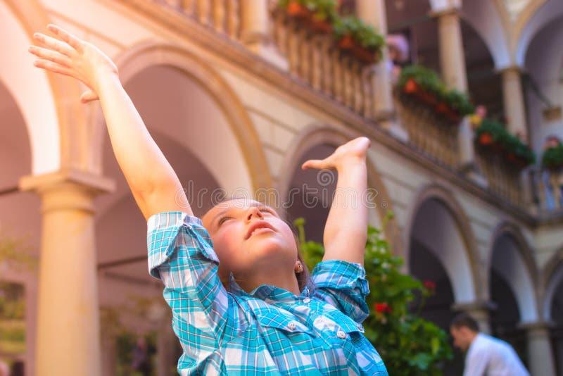 La muchacha aumenta sus brazos admiringly hasta la luz del sol imagenes de archivo