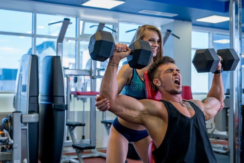 La muchacha ayuda al individuo muscular a ejercitar con pesas de gimnasia foto de archivo