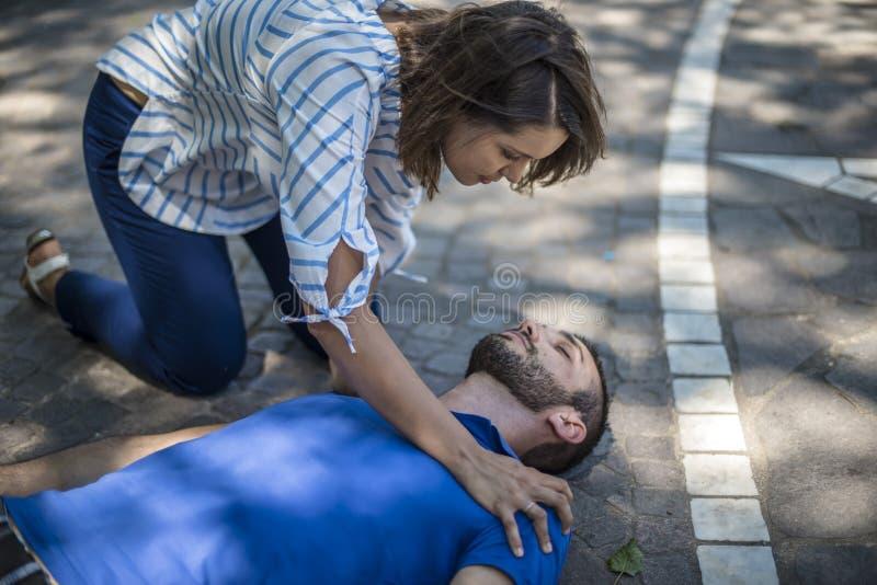 La muchacha ayuda a un individuo inconsciente después de accidente imagen de archivo