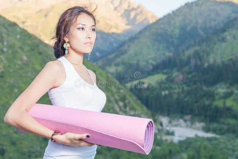 La muchacha bastante asiática con la estera de la yoga que va a la aptitud ejercita imagen de archivo libre de regalías