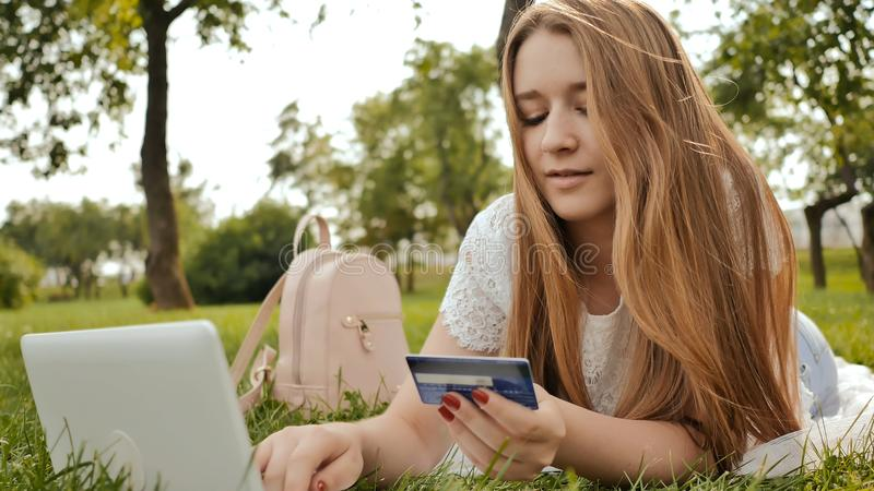 La muchacha bastante joven del estudiante hace compras en línea usando una tarjeta y un ordenador portátil de crédito fotos de archivo libres de regalías