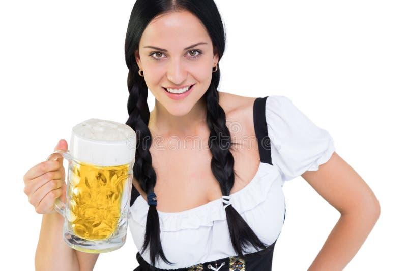 La muchacha bastante más oktoberfest que sostiene la jarra de cerveza de la cerveza foto de archivo