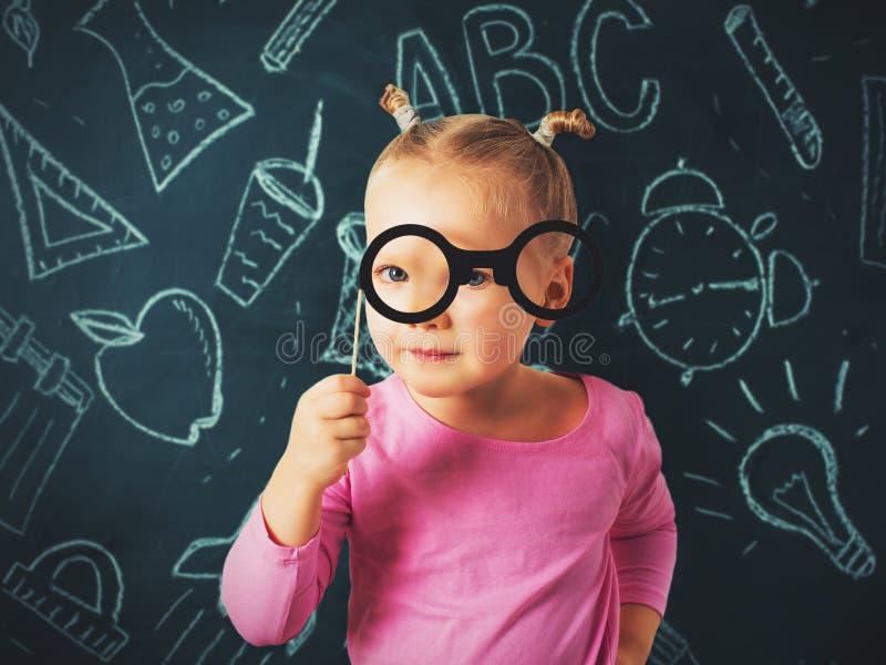 La muchacha bastante pequeña investiga algo a través de los vidrios en tiza foto de archivo