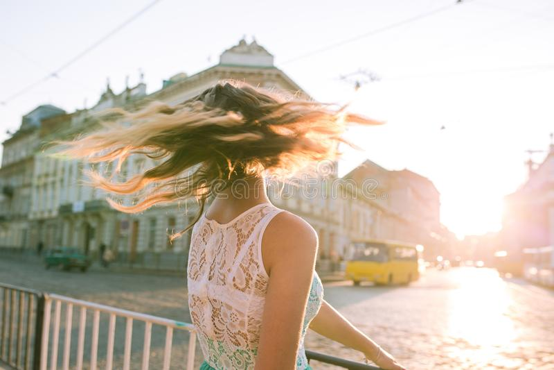 La muchacha bastante rubia con el pelo que agita que presenta en sol irradia en th imagenes de archivo