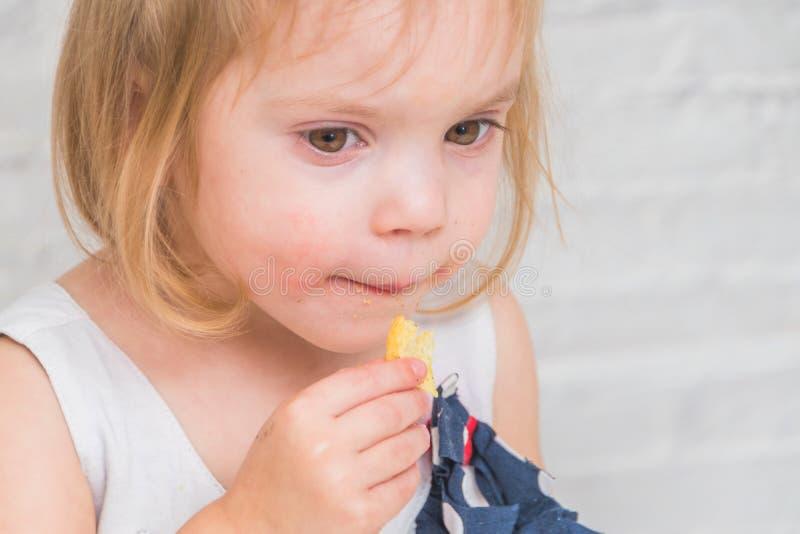 La muchacha, bebé come las patatas fritas, comida no sana, en bric blanco imagen de archivo