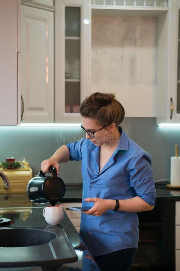 La muchacha bebe la bebida caliente en cocina fotos de archivo
