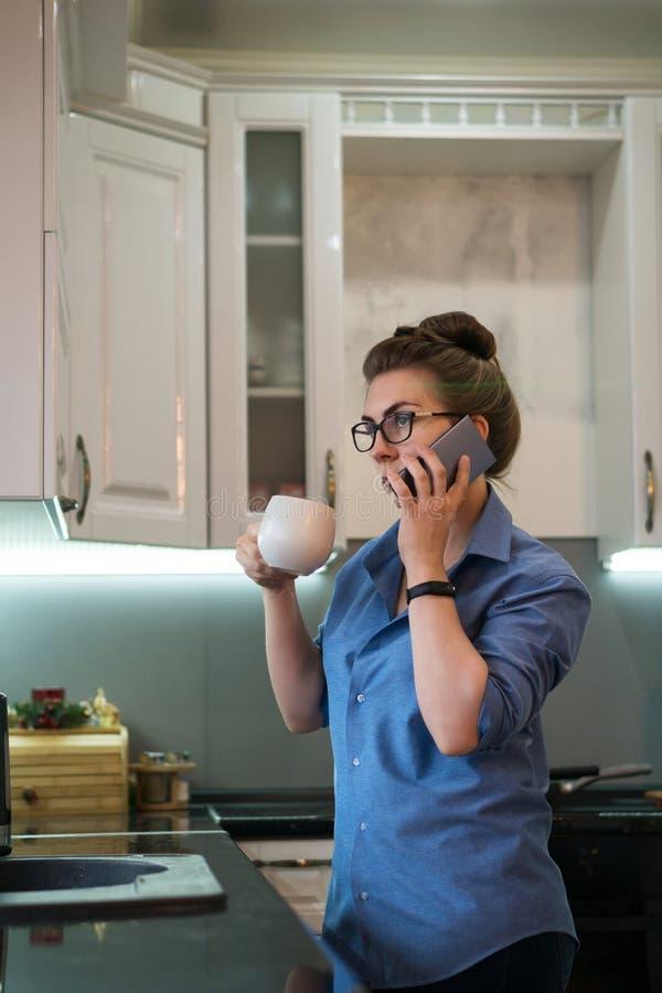 La muchacha bebe la bebida caliente en cocina foto de archivo libre de regalías