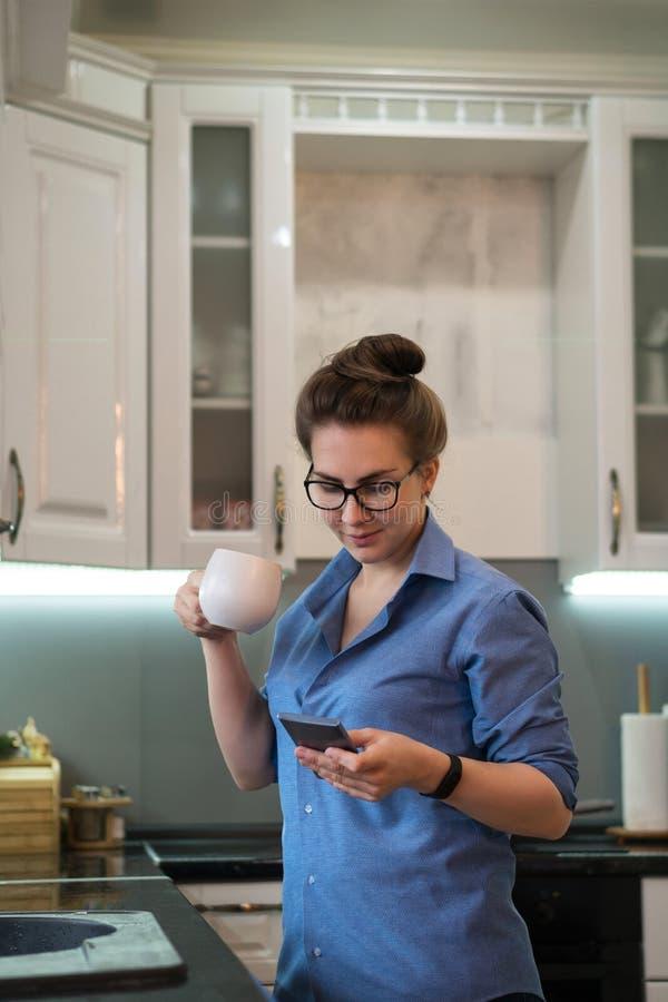 La muchacha bebe la bebida caliente en cocina fotografía de archivo