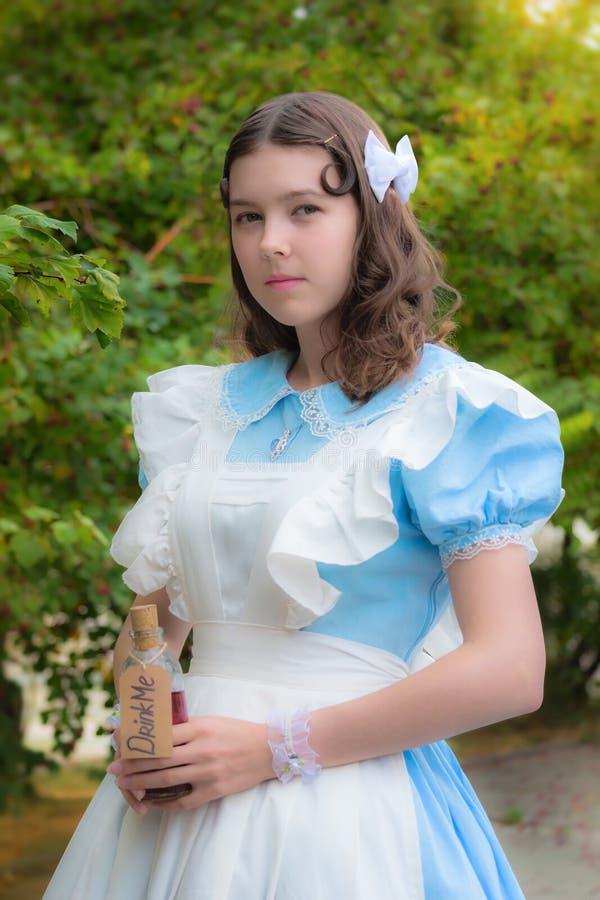 La muchacha bebe la bebida de los glas del color de la cereza imagen de archivo libre de regalías