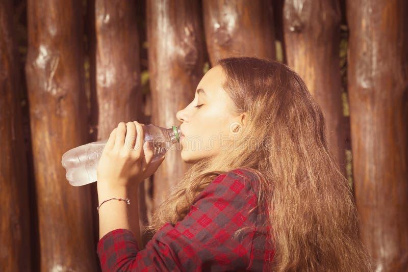 La muchacha bebe el agua fotos de archivo