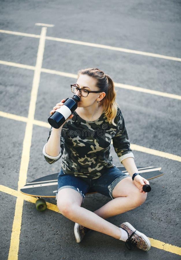 La muchacha bebe el agua de la botella fotografía de archivo