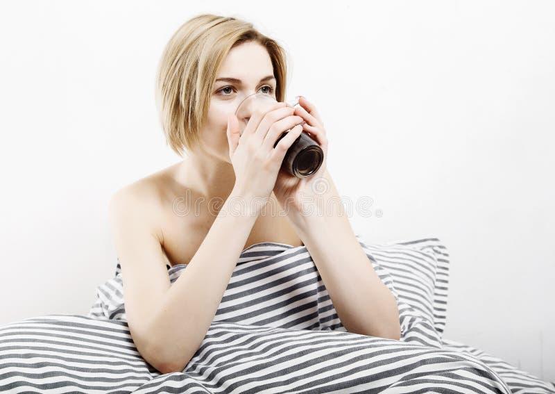 La muchacha bebe el café en cama Muchacha de la mañana que la chica joven despierta por la mañana sueño Mañana que despierta Leye fotos de archivo libres de regalías