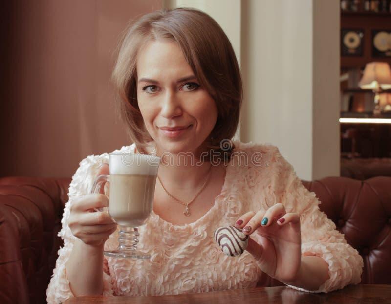 La muchacha bebe el latte con las galletas fotos de archivo libres de regalías