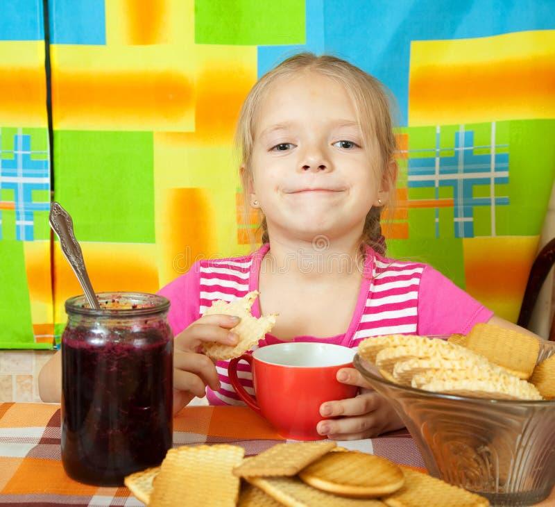 La muchacha bebe té con la galleta imagen de archivo libre de regalías