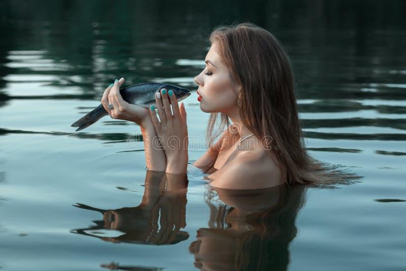 La muchacha besa un pescado foto de archivo