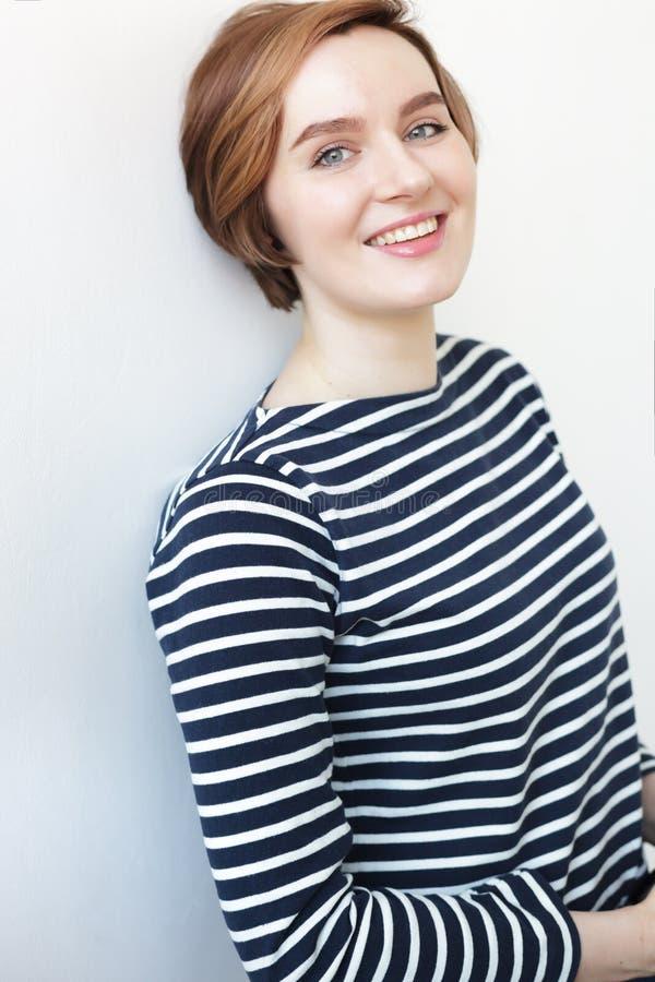 La muchacha blanca hermosa en una camiseta rayada sonríe imagen de archivo