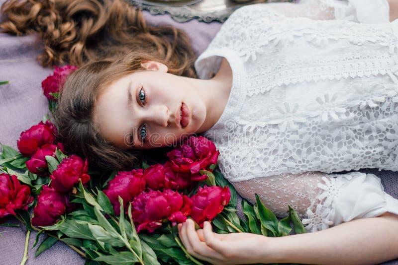 La muchacha blanda con los ojos azules acerca a peonías púrpuras fotos de archivo libres de regalías