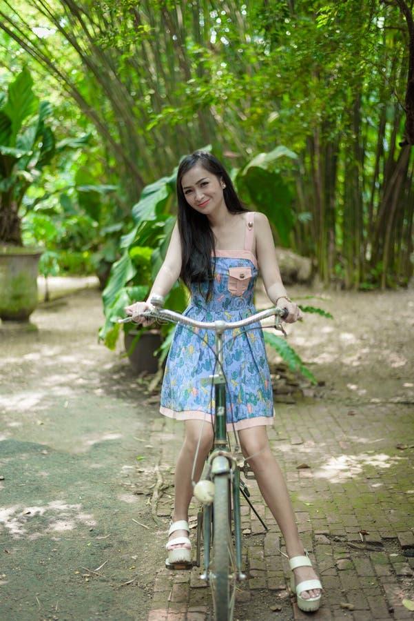 La muchacha bonita asiática tiene biking una bicicleta con feliz y sonrisa en el pequeño café del jardín del árbol, provincia de  imagenes de archivo