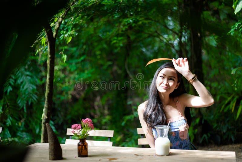 La muchacha bonita asiática tiene leche blanca drinkling del hielo con feliz y el SM foto de archivo libre de regalías