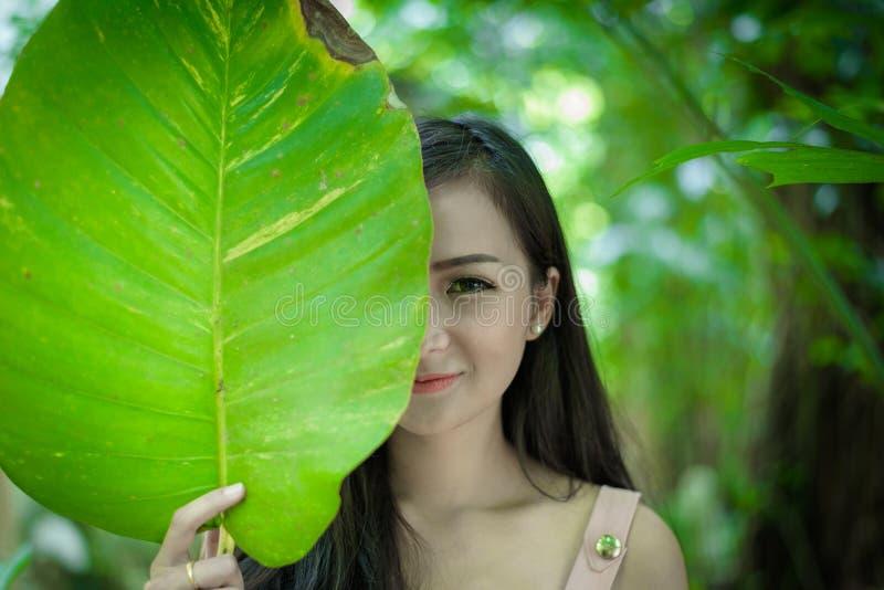 La muchacha bonita asiática tiene ojo derecho cerrado con cierre encima del concepto en el pequeño café del jardín del árbol, pro imagen de archivo libre de regalías