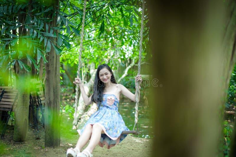 La muchacha bonita asiática tiene relajación con el oscilación en el pequeño café del jardín del árbol, provincia de Nakhon Patho imagen de archivo libre de regalías